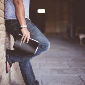 Man stood against wall with bible in hand